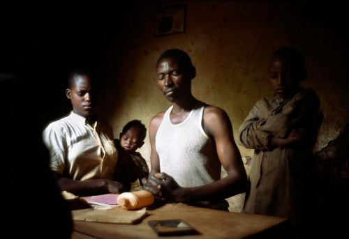 Rwanda - Kibileze - Narcisse prays with his family at home, Photo Stuart Freedman