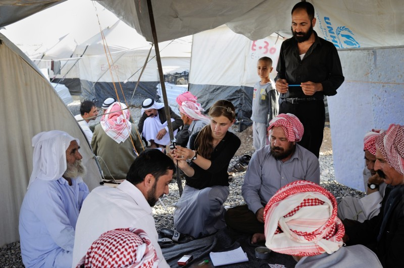 Bushra, 16, takes a photo of men playing cards in her camp. Photo: UNICEF/Iraq/2015/Mackenzie